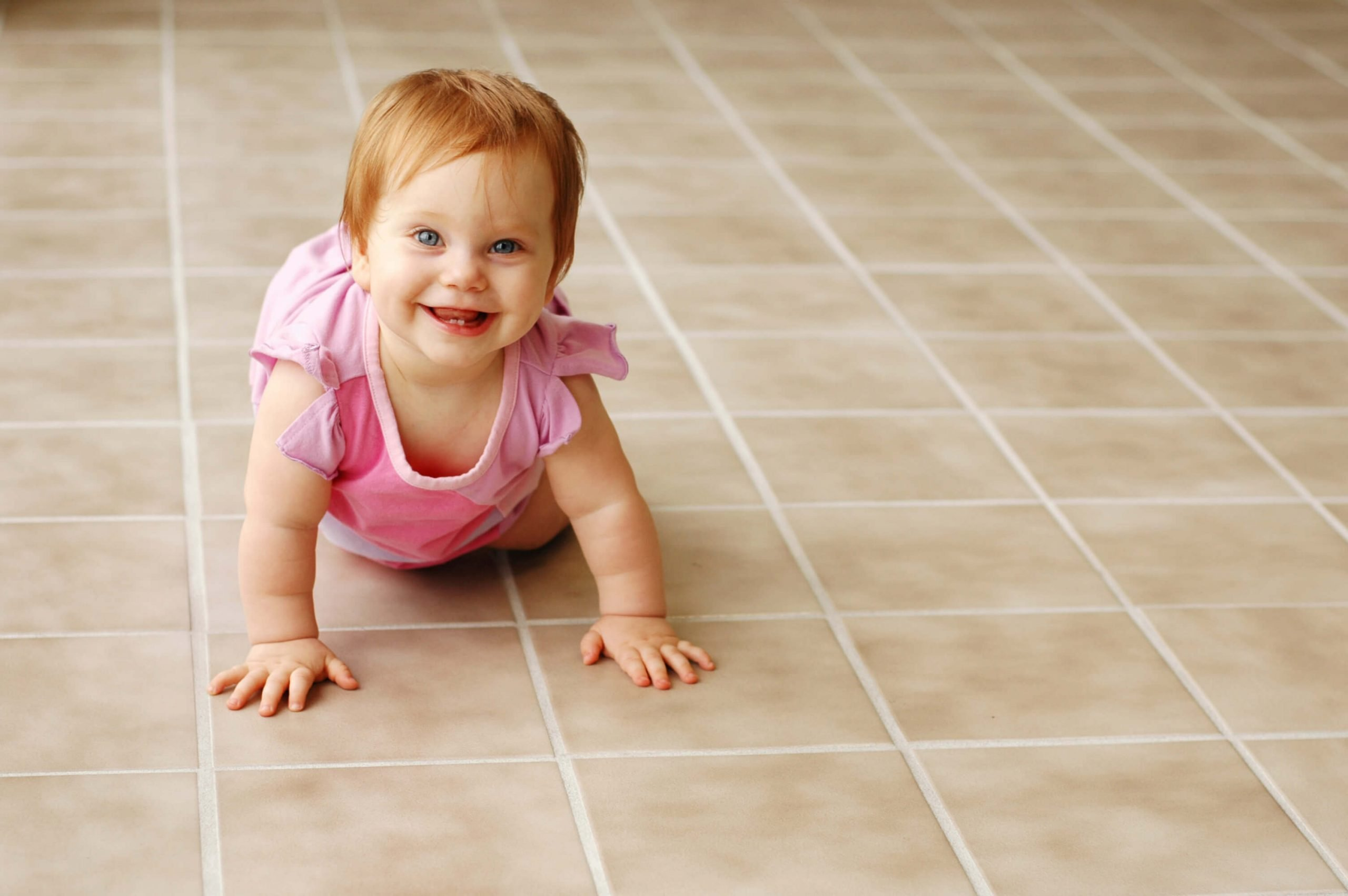 baby crawling on kitchen tile floor