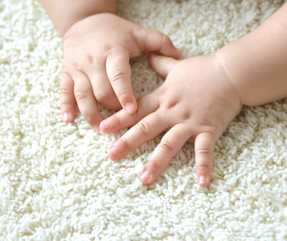 Baby hands on clean carpet