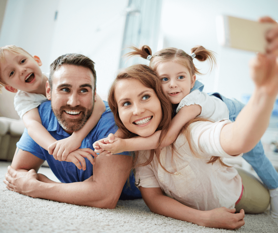 family smiling together on carpet taking picture on phone